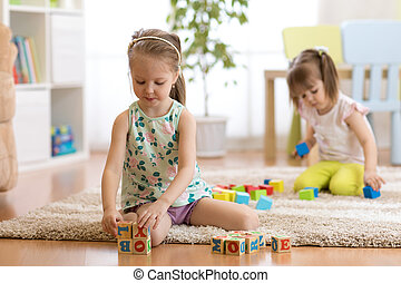 Children toddlers girls play toys at home, kindergarten or daycare centre.
