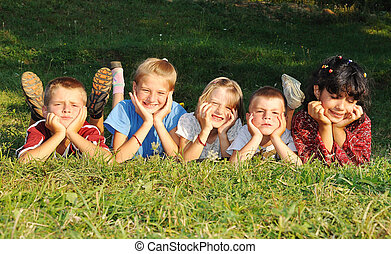 Children together, happiness on green meadow in summer time