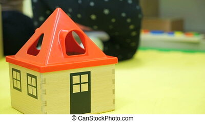 Children toy house with red roof on the floor