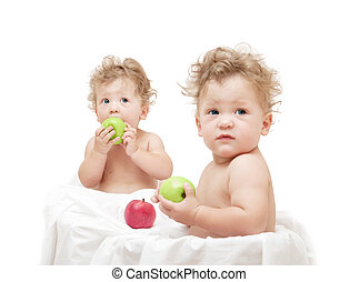 children twins eating a green apple on white background