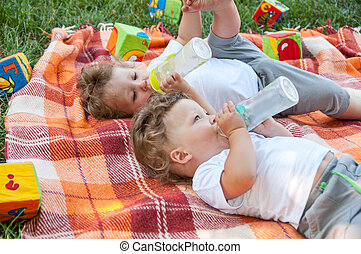 children twins lay on the coverlet among the toys and drink wate