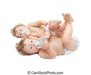 children twins lying suck milk bottles on white background