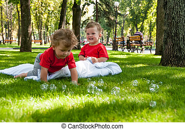 children twins play on the grass with soap bubbles
