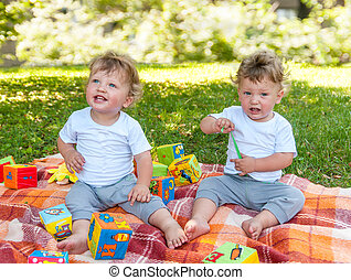 children twins sitting on a blanket among the toys in nature