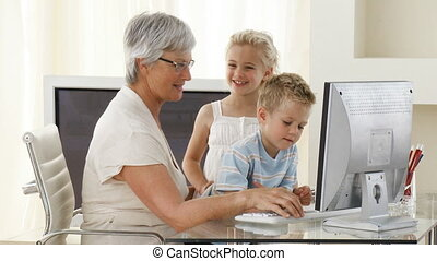 Children using a computer with their grandmother
