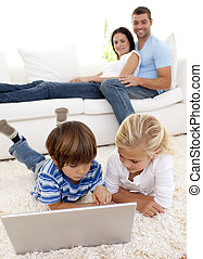 Children using a laptop and couple lying on sofa - Children...
