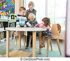 Children Using Digital Tablet At Table In Library