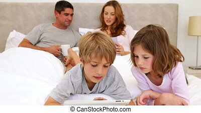 Children using tablet in bed with parents