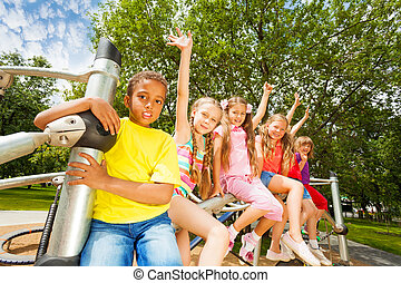 Children waiving hands sitting on round bar