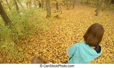 Children walk along the yellow foliage