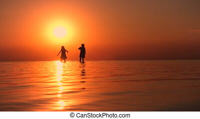 children walking by the sea at the sunset time