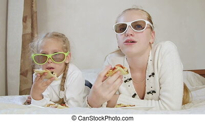 Children watching 3d TV shows and eating pizza lying on the bed