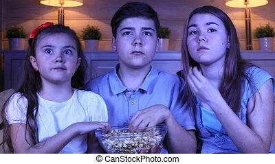 Children watching a horror film on TV - Group of children...