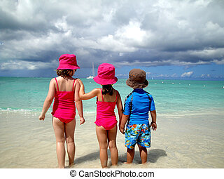 children watching waves roll in on a warm sunny beach