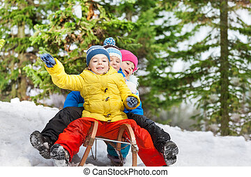 Children winter fun on sledge sliding down