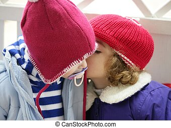 Children, winter red hat whispering in ear