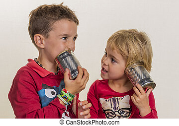 children with a can telephone - two small children are ...