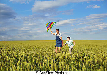 Children with a kite run across the wheat field in the summer. C