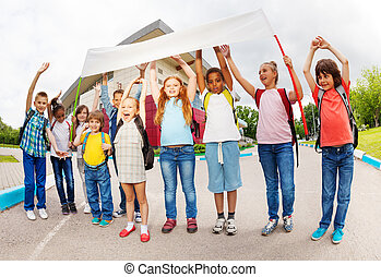 Happy children with arms up holding placard standing near school building during summer day time