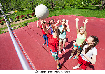 Children with arms up to ball play volleyball
