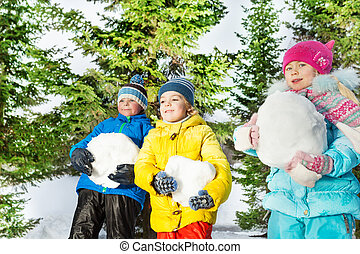 Children with big snowballs in the forest