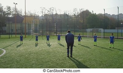 Children with coach during warm up of soccer team - Young ...