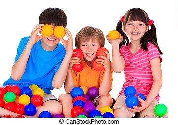 Children posing with colorful plastic balls, on white studio background.