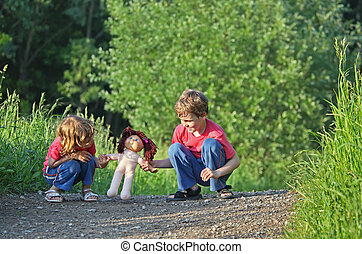 Children with doll on path in park