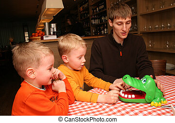 children with father play in cafe