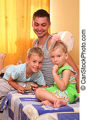 Children with father sitting on bed in room