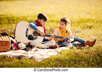 Children with guitar in park