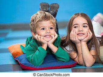 Children With Head In Hands Lying On Floor In Classroom -...