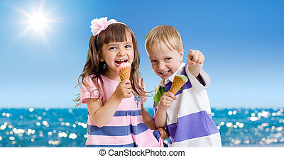 Children with icecream cone outdoor on seashore in hot summer day