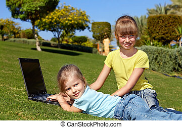 Children with laptop on green grass.