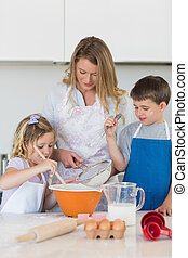 Children with mother baking cookies at counter top in...