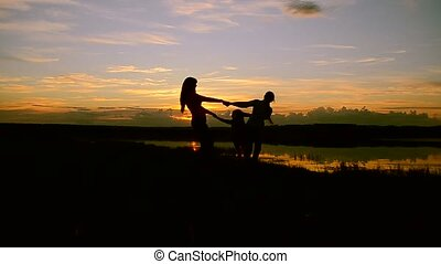 Children with mother whirl on the shore at sunset