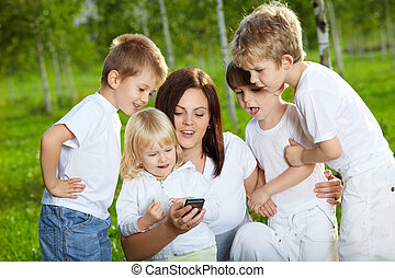 Four small child and mother are interested by a mobile phone in a summer garden