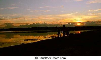 Children with mum walk on the beach at sunset