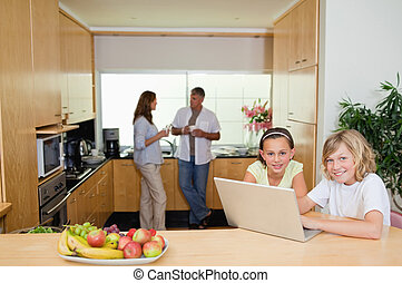 Children with notebook in the kitchen and parents behind them