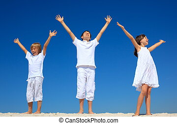 Three children wearing white clothes with arms outstretched as they stand on a beach against a blue sky.