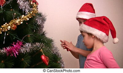 children with red hats hangs up fur-tree toy on christmas tree