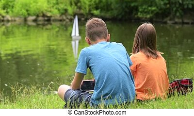 Children with remote controlled boat