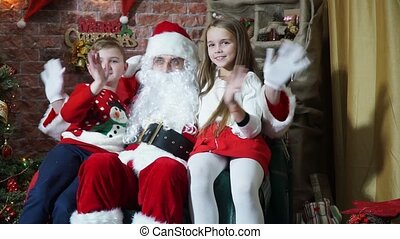 Children with Santa Claus sitting on a chair and waving their hands