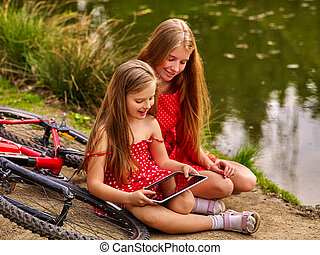 Children with tablet pc near bicycle into river in park .