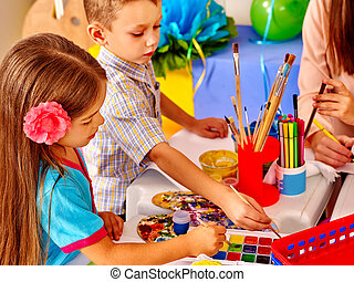Children with teacher woman painting on paper at table in kindergarten . Two kids and one adult.