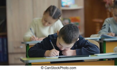 Children write sitting at a desk - Children write while...