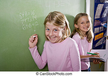 Children writing on blackboard in classroom - Back to school...