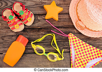 Children's beach accessories on the old wooden background. Toned image.