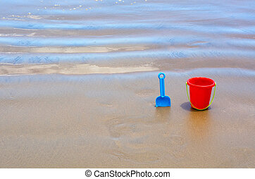 Children's beach toys, red bucket and blue spade on sand...