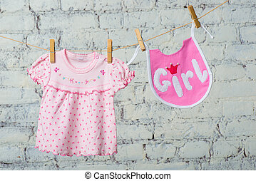 Children's bib and dress for the girl, dry on a rope on a white brick wall.